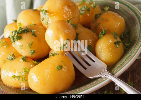 caramelized new potatoes with herbs close-up on a plate. horizontal, rustic - Stock Photo