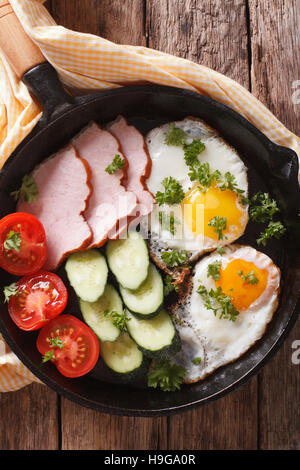 fried eggs with ham and fresh vegetables close-up in a frying pan on the table. vertical view from above - Stock Photo