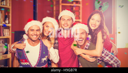 Composite image of portrait of men with christmas wearing giving women piggyback rides - Stock Photo
