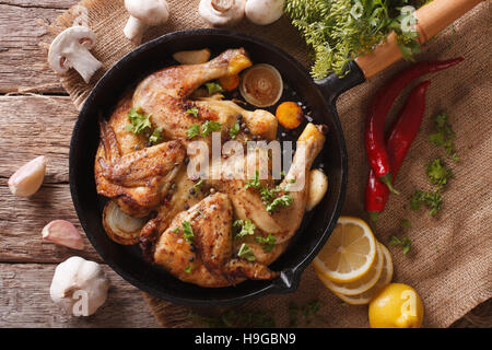 Hot Fried Chicken Tabaka with ingredients close-up on the table. horizontal view from above - Stock Photo