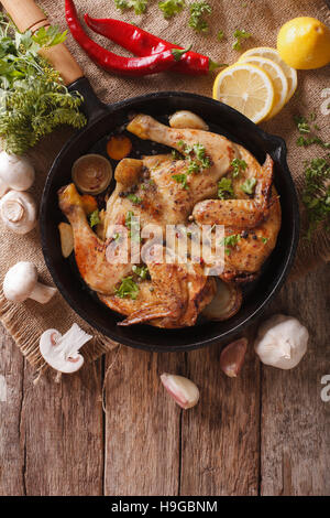Hot Fried Chicken tobacco with herbs and garlic in a pan close-up. Vertical view from above - Stock Photo