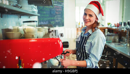 Composite image of portrait of happy waitress wearing santa hat - Stock Photo