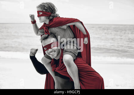 Father and son in superhero costume pretending to run - Stock Photo