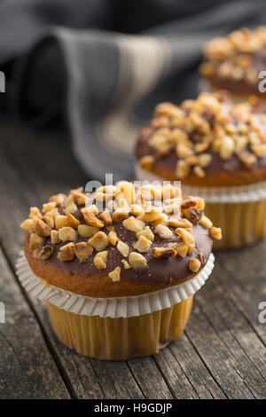 Sweet hazelnut muffins on old wooden table. - Stock Photo