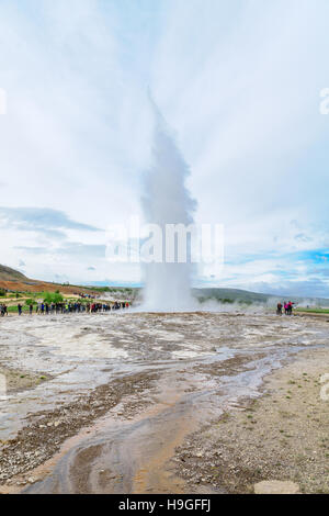 GEYSIR, ICELAND - JUNE 11, 2016: Tourists watching an eruption of the Strokkur geyser, in Geysir, Iceland - Stock Photo