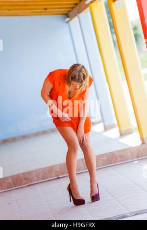 Pulling her dress exposing leg standing stand looking down angled shot corridor outdoors awkward position bending - Stock Photo