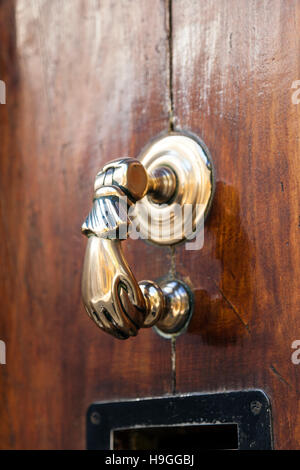 A gold hand-shaped door knocker - Stock Photo