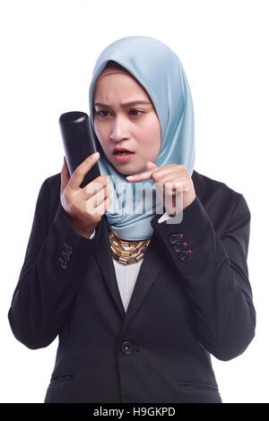 angry businesswomen while pointing her finger to the phone isolated on white background - Stock Photo