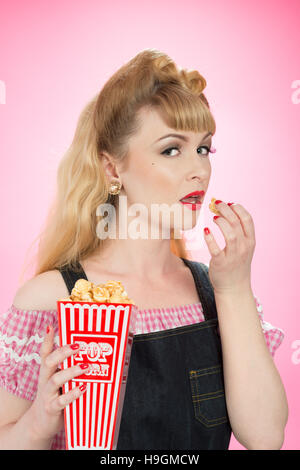Pin up girl eating from a carton of popcorn - Stock Photo