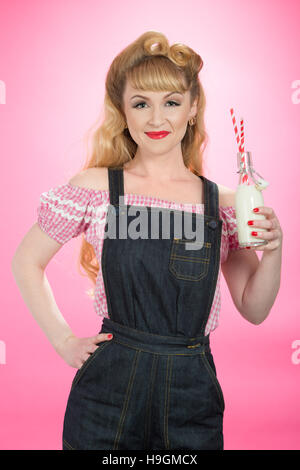 Pin Up girl drinking milk from a retro swing top bottle with straws - Stock Photo
