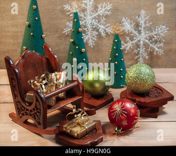 Gifts for the holiday in a wooden chair with Christmas toys and balls beside Christmas trees made of felt on a wooden - Stock Photo