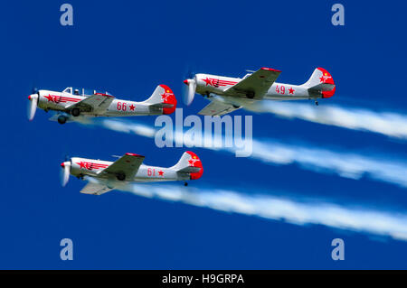 Three Pilatus P2 WW2 era training airplanes fly in formation with smoke trails. - Stock Photo
