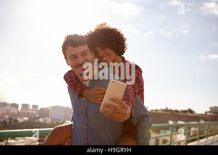 Laughing piggy back riding girl taking a selfie of them while sitting on her boyfriend back holding on with her - Stock Photo