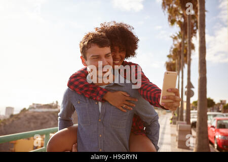 Piggy back riding girl taking a selfie of them while sitting on her boyfriends back holding on with her right hand - Stock Photo