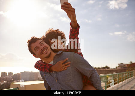 Piggy back riding girl with open mouth, taking a selfie of them while sitting on her boyfriend back holding on with - Stock Photo