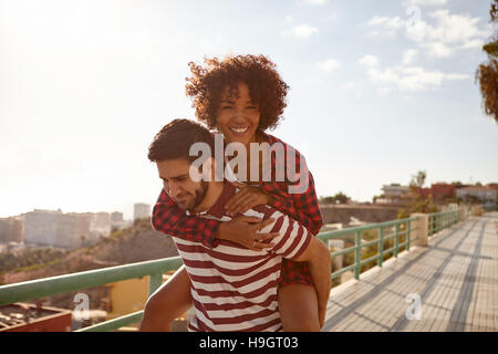 Couple doing the piggy back ride with her on his back, right arm around his neck, left hand on his shoulder and - Stock Photo