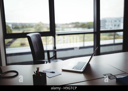 Laptop, pen holder and notepad on desk - Stock Photo