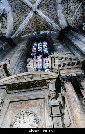 Ornate carvings and stained glass window  inside the Duomo Milano (Milan Cathedral), Italy - Stock Photo