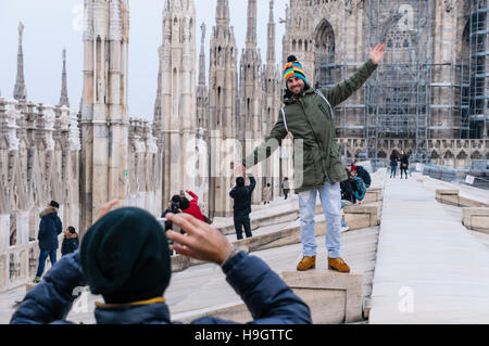 A man has his photograph taken on the roof of the Duomo Milano (Milan Cathedral), Italy. - Stock Photo