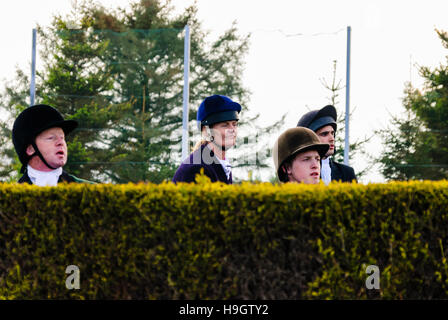 Horse riders from a rural foxhunting group looking over a high hedge - Stock Photo