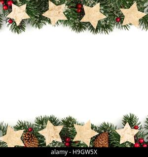 Christmas double border of branches with rustic wood star ornaments over a white background - Stock Photo