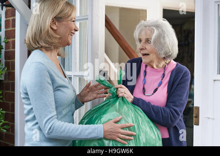 Woman Taking Out Trash For Elderly Neighbour - Stock Photo