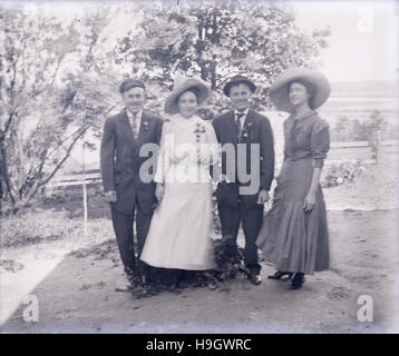 Antique c1900 photograph, two couples in late Victorian dress. Long shutter exposure created slight motion blur. - Stock Photo