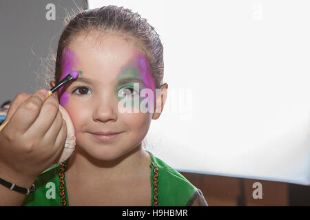 Little smiling girl making facepaint before halloween party. The make-up artist is applying some colors - Stock Photo