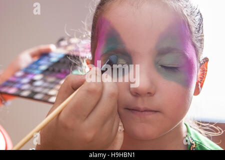 Little cute girl making facepaint before halloween party. The make-up artist is applying some colors while she closes - Stock Photo