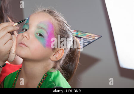 Little cute girl making facepaint before halloween party. The make-up artist is applying some colors while she is - Stock Photo