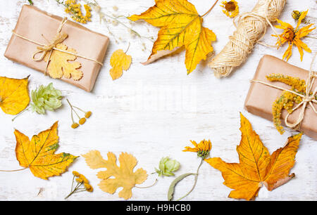 Composition of gifts and yellow leaves on a white wooden background. concept autumn - Stock Photo