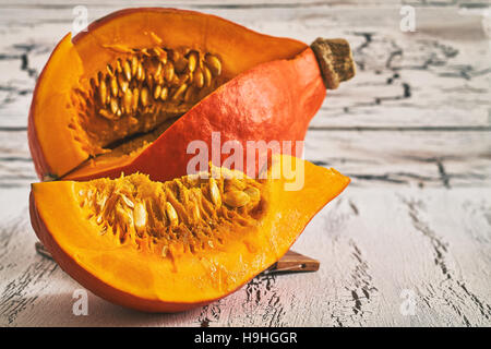 Red kuri squash (Hokkaido pumpkin) on white rustic wooden background - Stock Photo