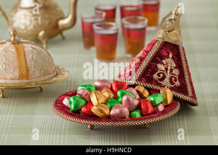 Moroccan festive sweets in a red tajine and tea - Stock Photo