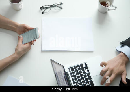 Office desk top view, woman with phone, man on laptop - Stock Photo