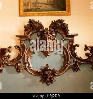 The carved pine bedhead in the mid 18th century rococo style of Matthias Lock probably began life as a mirror frame. - Stock Photo