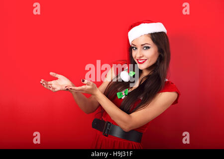 Happy smiling young woman in santa claus clothing holding and advertising something empty in the hands on red background - Stock Photo