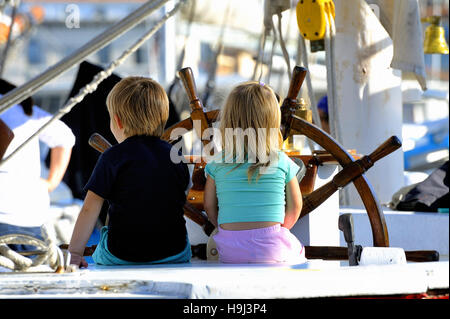 Two young children on the stand of an old wooden sailing ship cruising imagining in full - Stock Photo