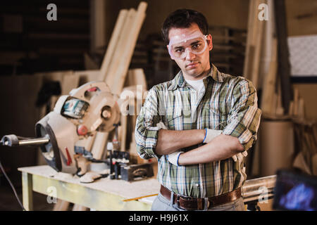 Handsome carpenter in protective glasses is looking at camera and smiling while standing near his wooden object - Stock Photo