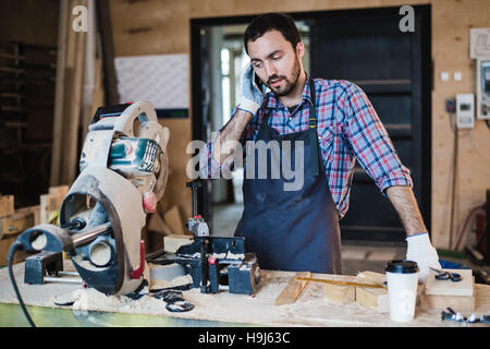 portrait of carpenter calling by smart phone at the workshop - Stock Photo