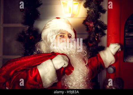 The real Santa Claus. Santa knocks on the door. Christmas night. - Stock Photo