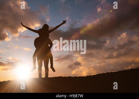 Composite image of happy casual man giving pretty girlfriend piggy back - Stock Photo