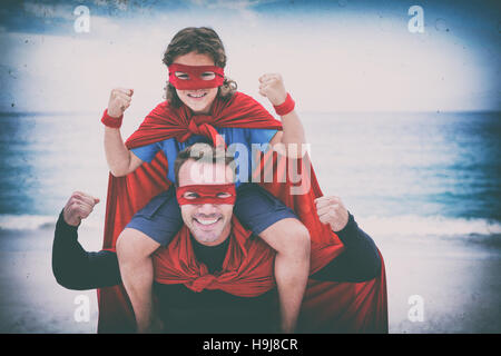 Father and son smiling while flexing muscles at sea shore - Stock Photo