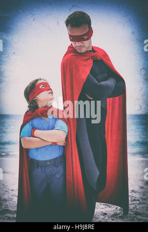 Father and son in superhero costume standing at beach - Stock Photo
