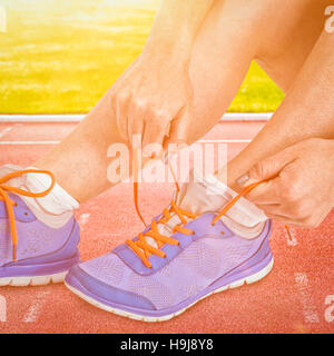 Composite image of athlete woman tying her running shoes - Stock Photo