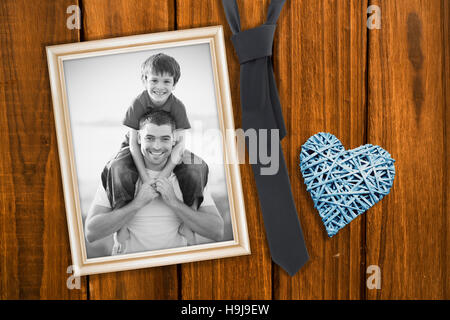 Composite image of father giving son piggyback ride - Stock Photo