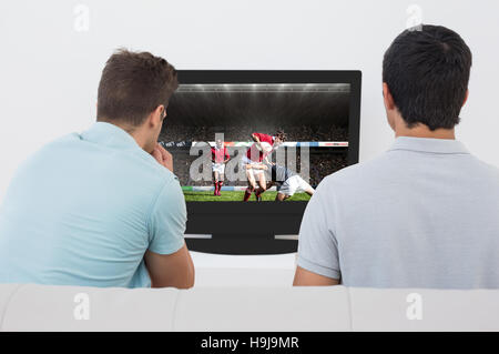 Composite image of two soccer fans watching tv - Stock Photo