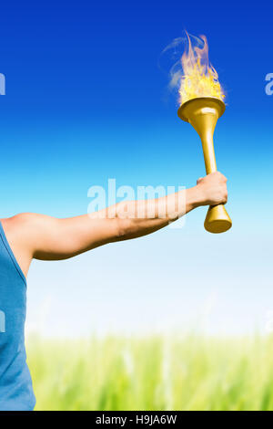 Composite image of rear view of athletic man holding the olympic torch - Stock Photo