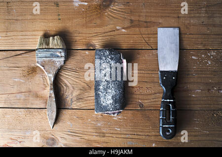 Old brush, sandpaper and trowel on a brown tattered wooden background, top view, joinery work, home repairs - Stock Photo