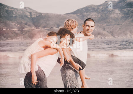Happy family playing on the beach - Stock Photo