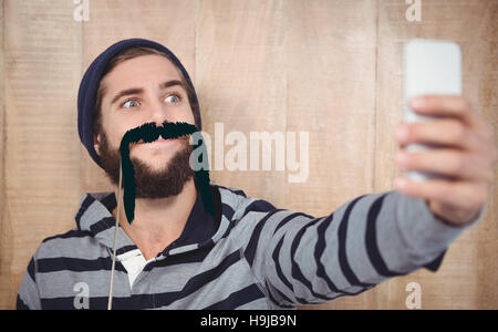 Composite image of hipster making face while taking selfie on mobile phone - Stock Photo